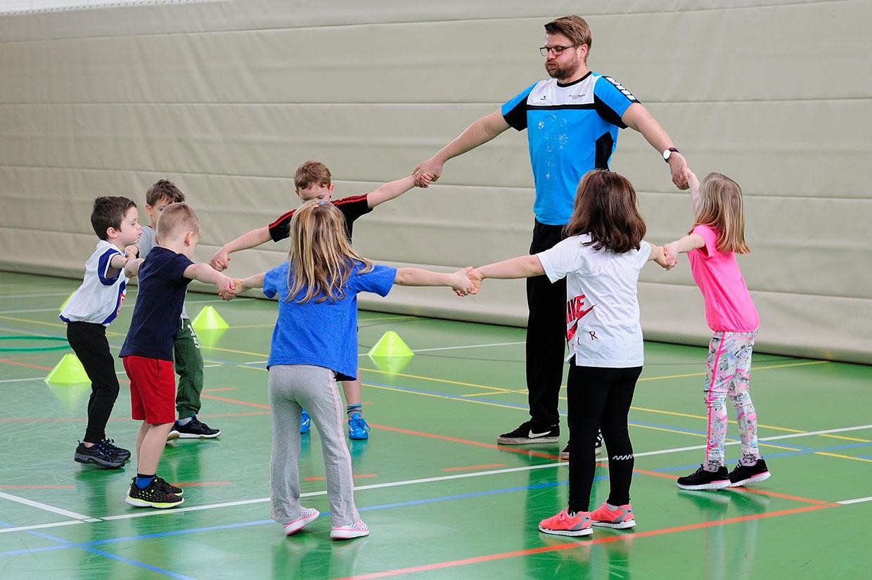 Bewegungsschule Kinder und Trainer im Kreis